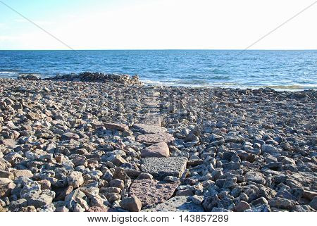 Stony coast with a footpath of flat stones leading to the water