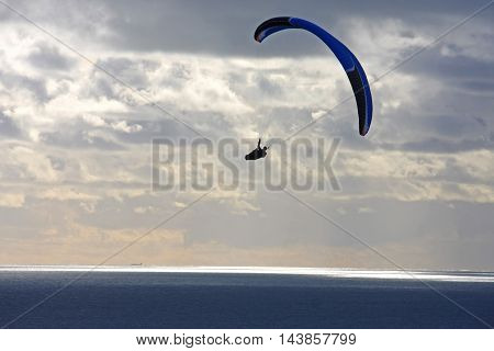 Paraglider flying his wing over the sea