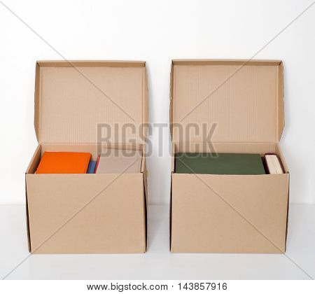 cardboard boxes full of books on the white wooden floor
