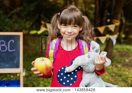 happy beautiful girl schoolgirl with an apple and an elephant. The concept of school and education