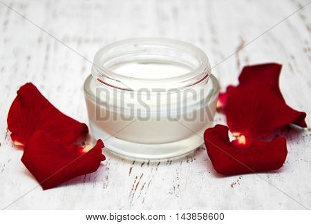 moisturizing cream and rose petals on a old wooden background