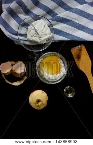 components of cooking cottage cheese cake (cottage cheese, flour, apple, egg, oil) on a black background