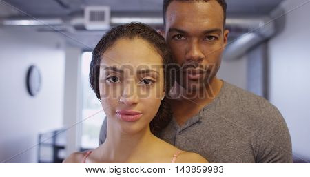 Black and Hispanic couple looking at camera standing in apartment