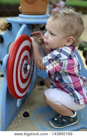 Curly Toddler Playing At Playground