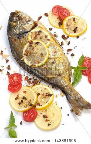 roasted fish Dorado with lemon slices and tomatoes flavored spices