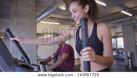 Hispanic woman working out on elliptical exercise machine in gym