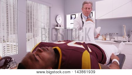 Mid-aged Physical Therapist Examining College Athlete Sports Injury