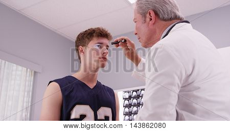 Senior Medical Doctor Checking Basketball Player's Eyes With Flashlight