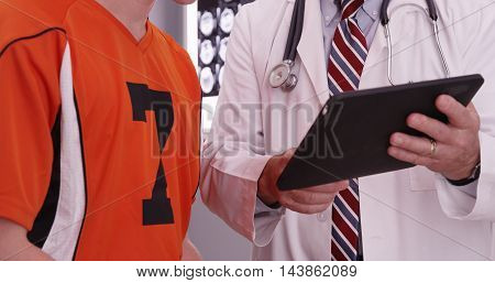 Portrait Of Medical Doctor Looking At Tablet Computer With College Athlete