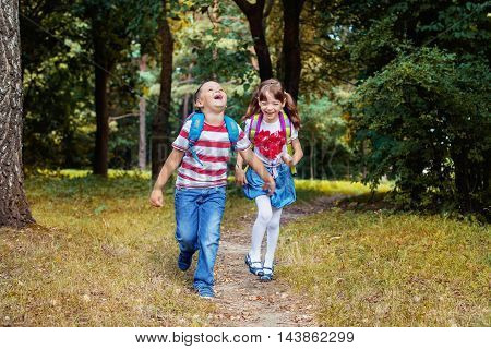little boy and girl running along the path
