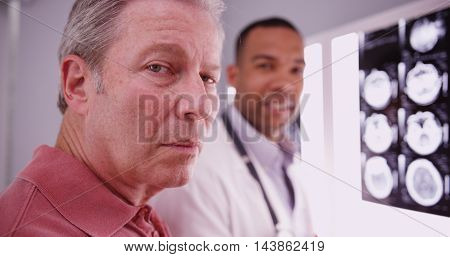 Senior Male Patient Looking At Camera With Young Medical Practitioner