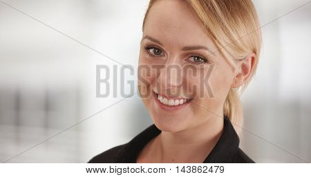 Happy businesswoman smiling at camera in the office