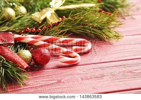 Christmax Tree Branch With Baubles, Candies On Red Wooden Table