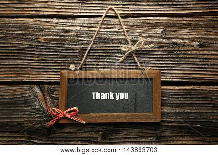 Brown wooden frame on brown wooden background, thank you