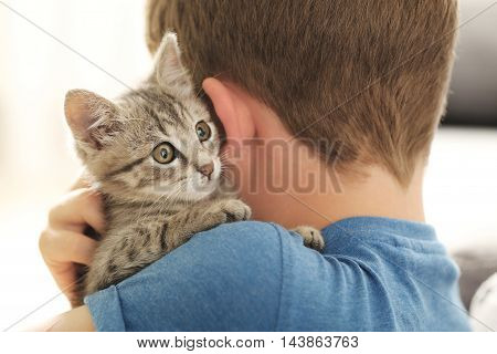 Child With Kitten On Hands At Home