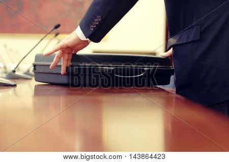 Business meeting detail businessman closing briefcase at the end of the meeting