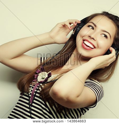 Young happy woman with headphones listening music over grey background
