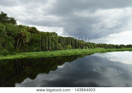 Storm clouds and shore line  reflection in water.