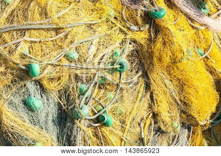 Yellow Fishing Net With Green Details Drying On A Pier
