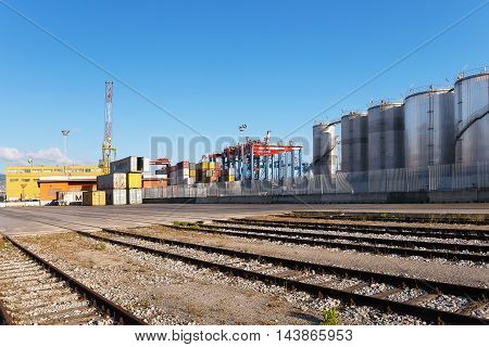 Naples Italy - August 10 2016: In the commercial port city some containers parked waiting for the goods to be distributed. In the background of the special cranes used for handling the heavy loads of goods unloaded from ships. On the right of the silos to