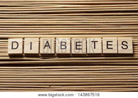 word diabetes on wooden cubes at wood background.