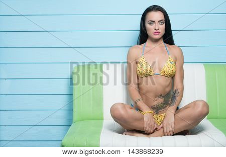Beautiful seductive brunette woman wearing yellow bikini looking into the camera while sitting on the leather sofa over blue wooden wall background