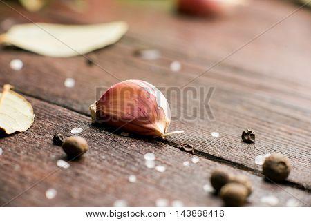 Salt, pepper, garlic and laurel on the brown wood surface. Closeup. Selective focus
