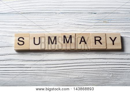 SUMMARY word written on wood block at wooden background.