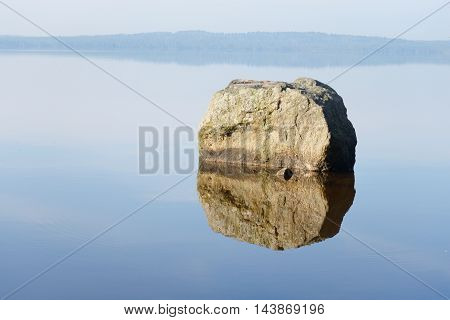Granite stone in a calm lake with reflection.