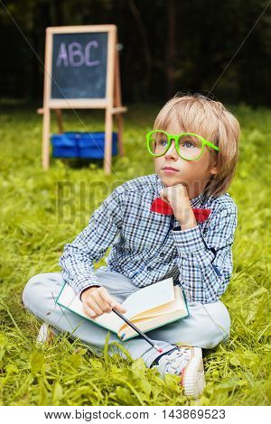 stylish little blond boy with glasses meditating