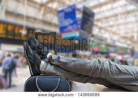 Delayed train concept. Tired and exhausted passenger is waiting on train with baggage in train station.