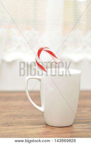 A candy cane in a white mug