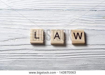 Law word written on wood block. Wooden ABC.