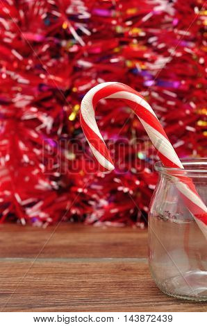 A candy cane in a jar with a red tinsel background
