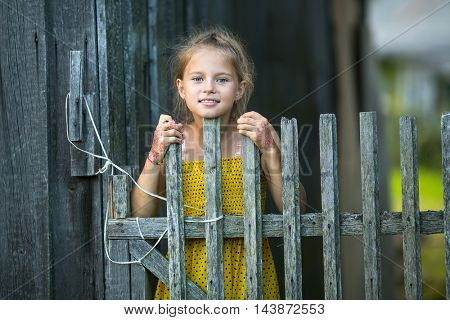 Portrait of cute little girl near the wooden fence in the village.