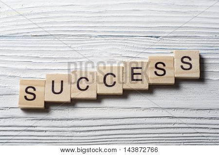 Success word written on wood abc block at wooden backround.