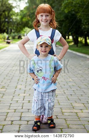 Sister and brother standing on the road in the park