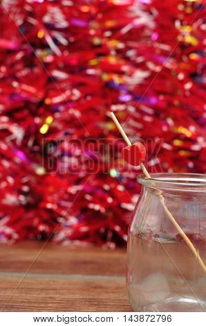 Valentine's Day. A red heart on a stick in a jar with a red background
