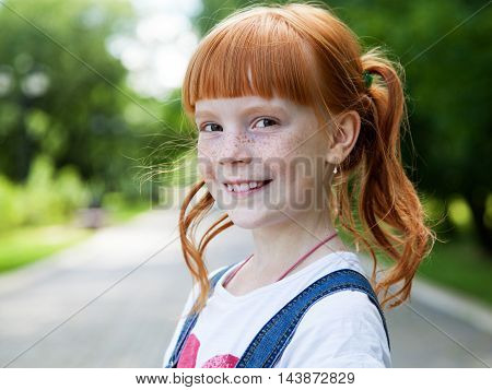 Close up portrait of a smiling ginger girl with freckles