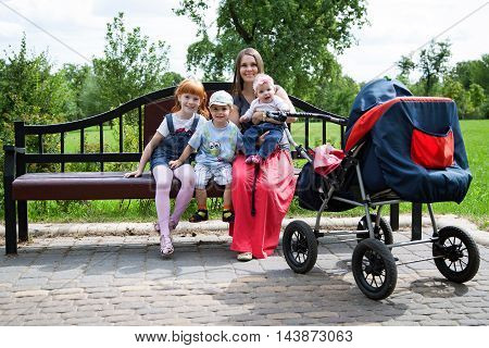 Mother with three children sitting on the bench in the park