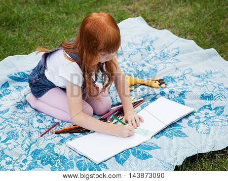 Little redhead girl drawing with pencils on the plaid on the lawn