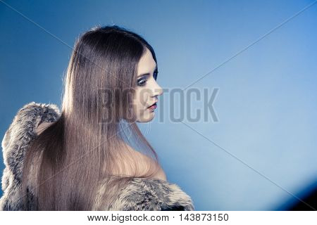 Portrait Of Girl With Long Hair. Young Woman In Fur Coat On Blue.