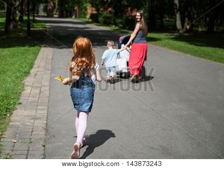 Little redhead girl catching up her family walking in the park view from the back