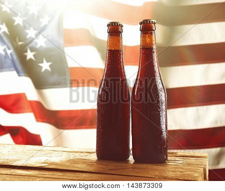 Two beer bottles on wooden table. USA flag background.