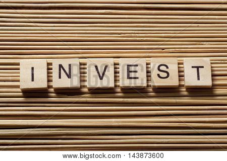 Invest word written on wood block. Wooden Abc.