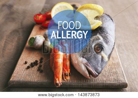 Allergy danger concept. Seafood with lemon slices on wooden cutting board. Text food allergy.