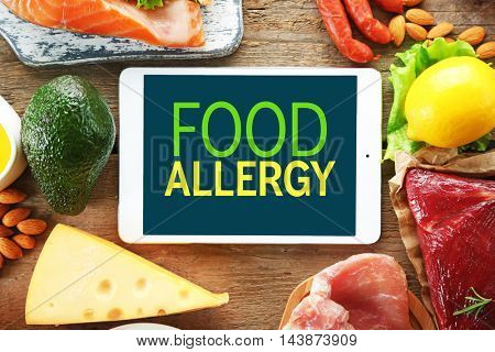Allergy danger concept. Tablet with text food allergy on screen. Different food on wooden background.