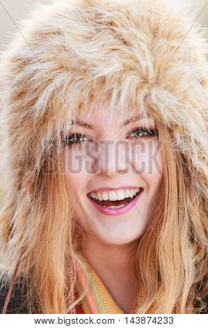 Portrait of pretty smiling fashionable woman in fall forest park. Happy gorgeous young girl in fur winter hat. Autumn fashion.