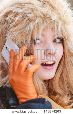 Smiling Woman In Fur Hat Talking On Mobile Phone.