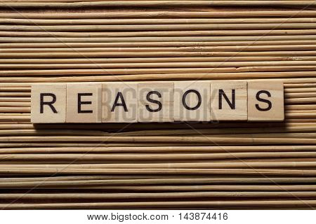 REASONS word written on wood abc block at wooden background.